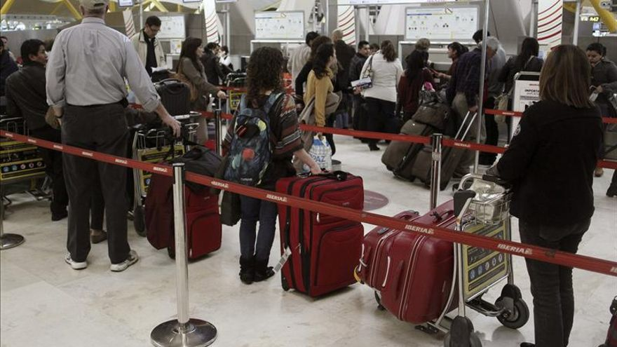 Pasajeros hacen cola en los terminales de facturación de Iberia de la T4 de Barajas Madrid. / EFE