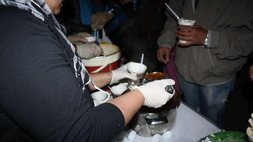 Voluntarios reparten la única comida de la noche para algunos refugiados financiada con donaciones. / FOTO: C. Negrete