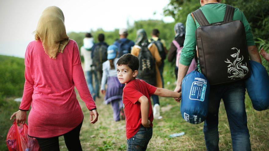 Los niños comieron unas galletas y unas ciruelas de las mochilas de sus madres en el camino del grupo de refugiados hacia el centro de Europa. / Foto: Jure Eržen.