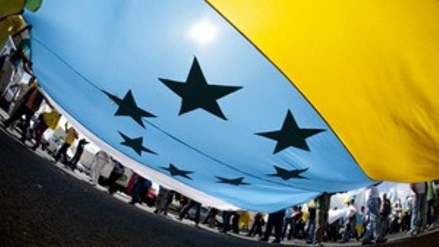 Manifestantes despliegan una bandera con las siete estrellas verdes. (ACN PRESS)