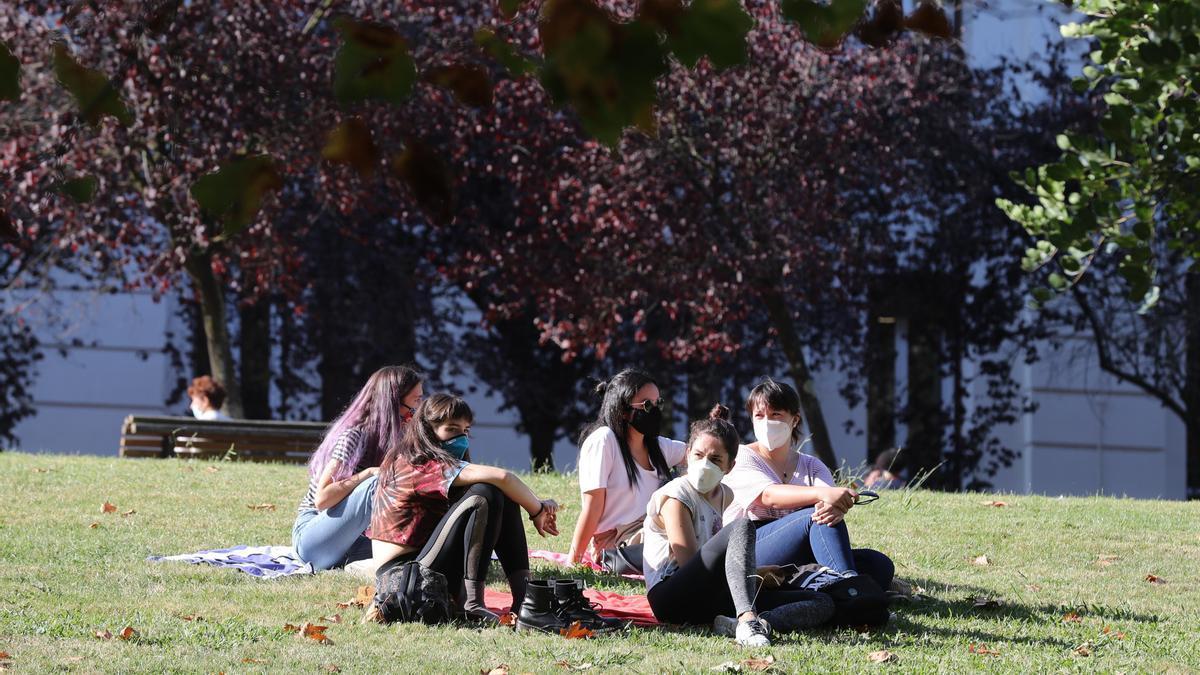 Varias estudiantes en un parque en Bilbao con hojas de otoño.