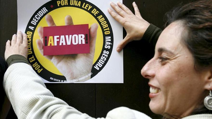 Una mujer pega un cartel en la puerta de la curia del Arzobispado de Granada durante una concentración de la Comisión Pro Derecho al Aborto. / Efe