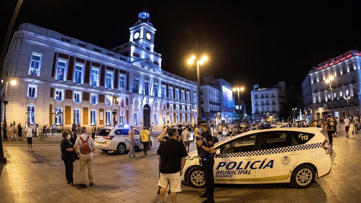 Varias personas celebran el fin del uso obligatorio de la mascarilla en espacios abiertos ante la Policía Municipal en la Puerta del Sol, en Madrid.