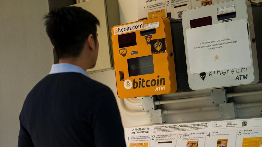 Un hombre observa un cajero Bitcoin en Wanchai, Hong Kong