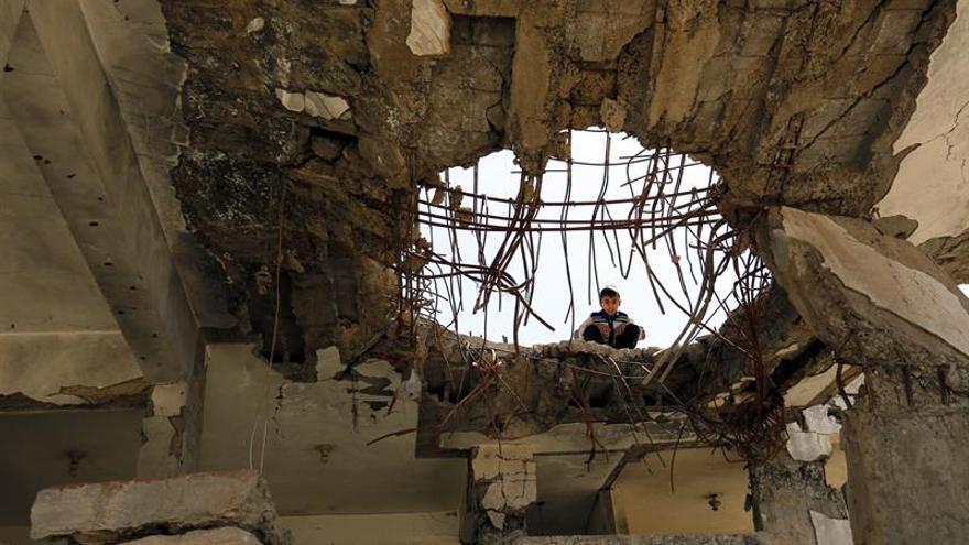 Un niño yemení mira a través de un agujero en el techo de una casa gravemente dañada que, según se informa, fue destruida por los ataques aéreos de Arabia Saudita en un barrio de Sana'a, Yemen, el 7 de octubre de 2017.