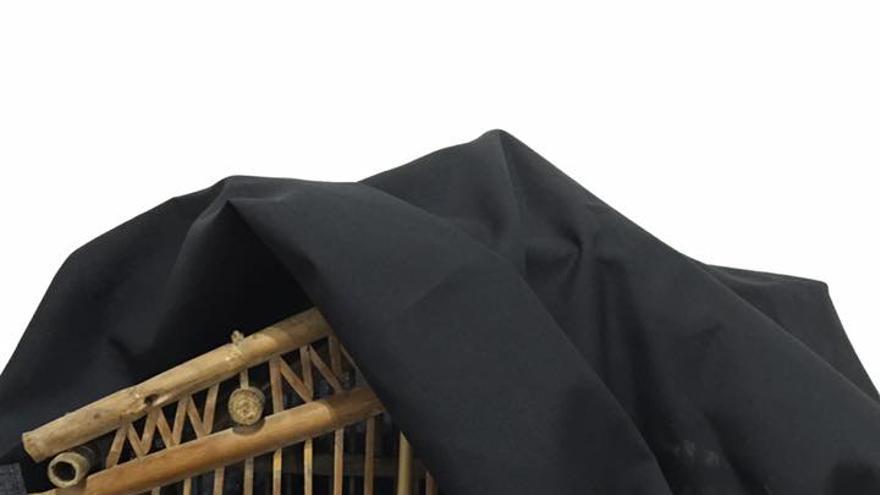 Jaula cubierta con una tela negra en señal de luto.