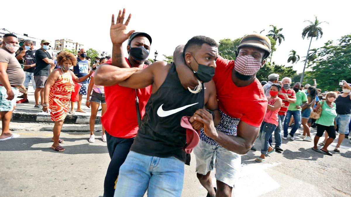 Dos personas detienen a un hombre durante una manifestación el domingo en La Habana.