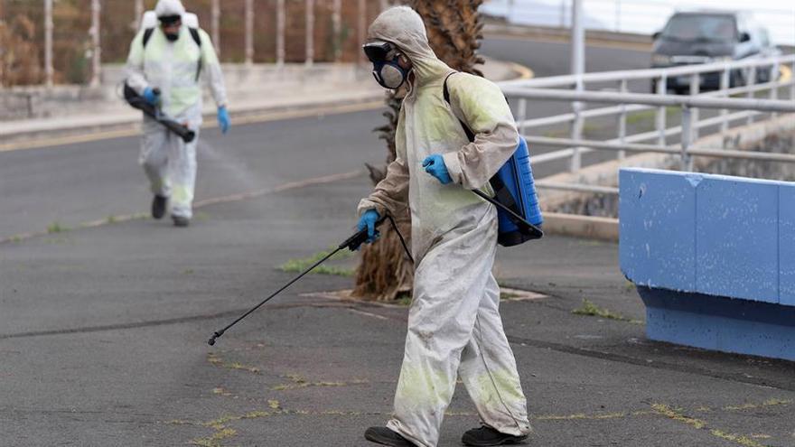 Personal del servicio de limpieza de la capital tinerfeña desinfecta la calle Nisamar del barrio de Añaza tras 20 días de la declaración del estado de alarma para frenar la expansión del coronavirus