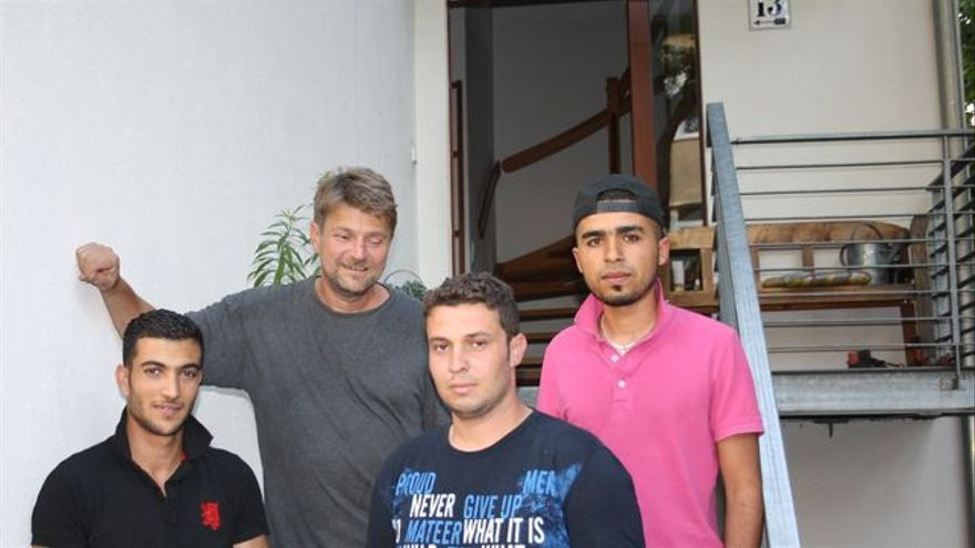 El periodista Bern Pickert con tres de los refugiados que ha acogido en su casa este fin de semana para que no tuvieran que dormir en la calle. / FOTO: C. Negrete