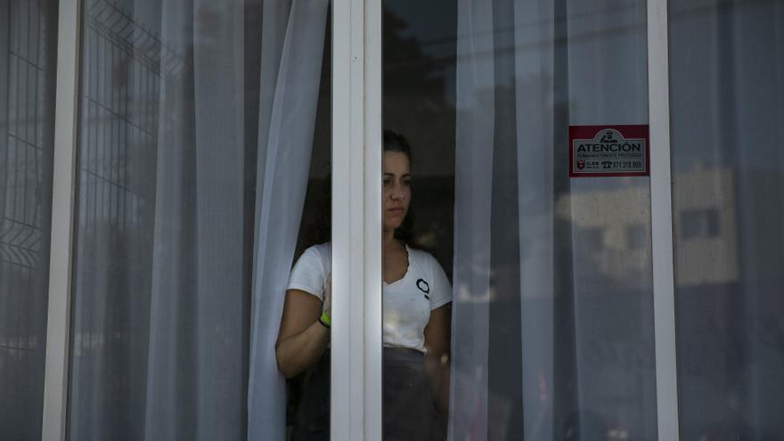 Una trabajadora de hotel observa, desde su puesto de trabajo, a un piquete de las 'kellys'