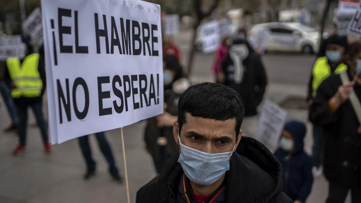 """""""El hambre no espera"""", se puede leer en el cartel de uno de los manifestantes cuando se cumplía un año del inicio de las colas del hambre en Madrid por la pandemia."""