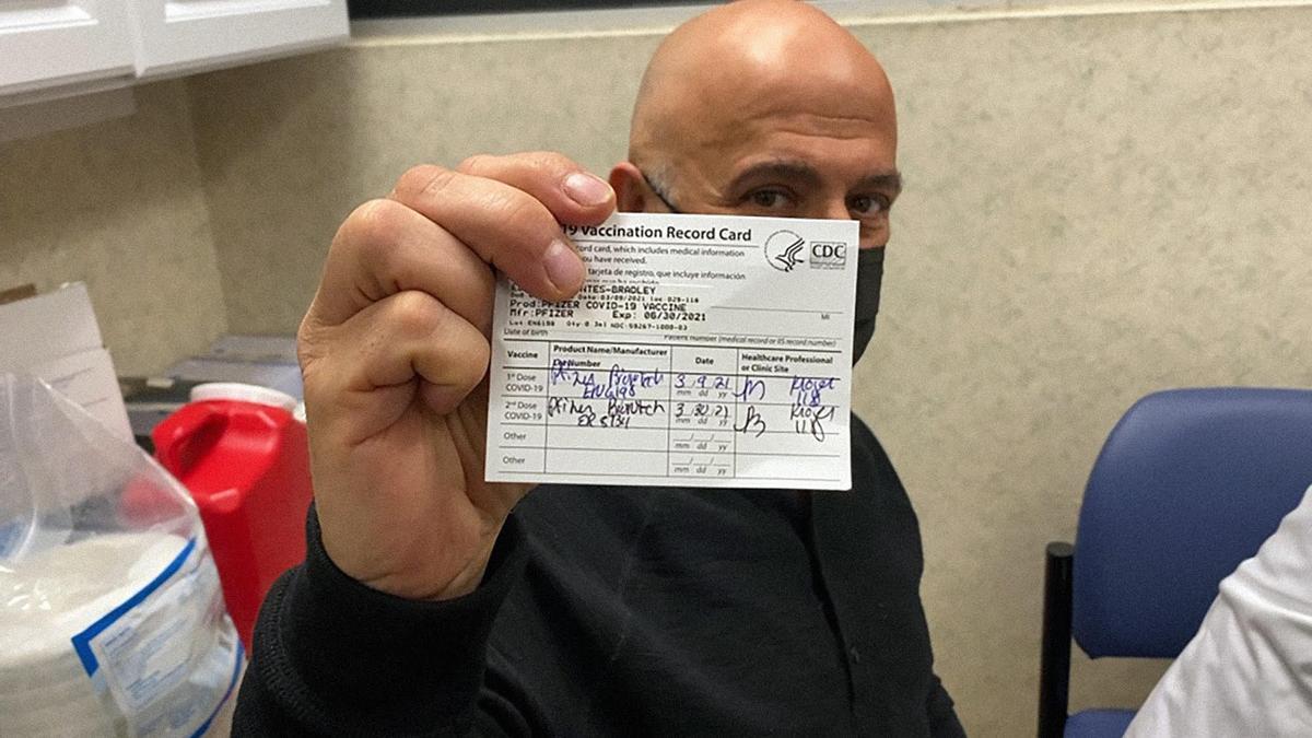 Eduardo Montes-Bradley muestra su carnet vacunatorio luego de recibir la dosis anti Covid-19.