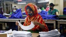 Una trabajadora cose con mascarilla en una de las fábricas textiles reabiertas en Dhaka, Bangladesh