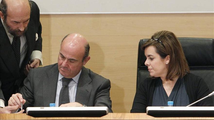 Soraya Sáenz de Santamaría y Luis de Guindos durante la firma del convenio por el que se constituye el Fondo Social de Vivienda (17 de enero de 2013). / Efe.