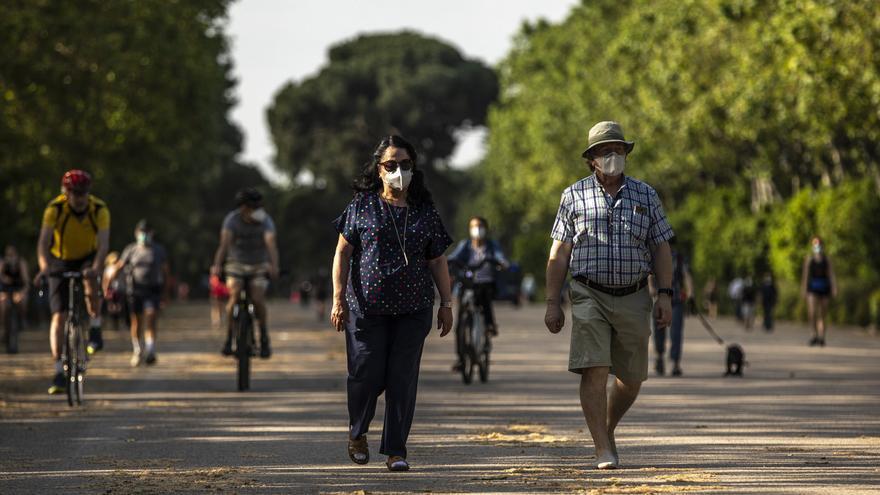 Dos personas con mascarilla paseando por el parque del Retiro, en Madrid