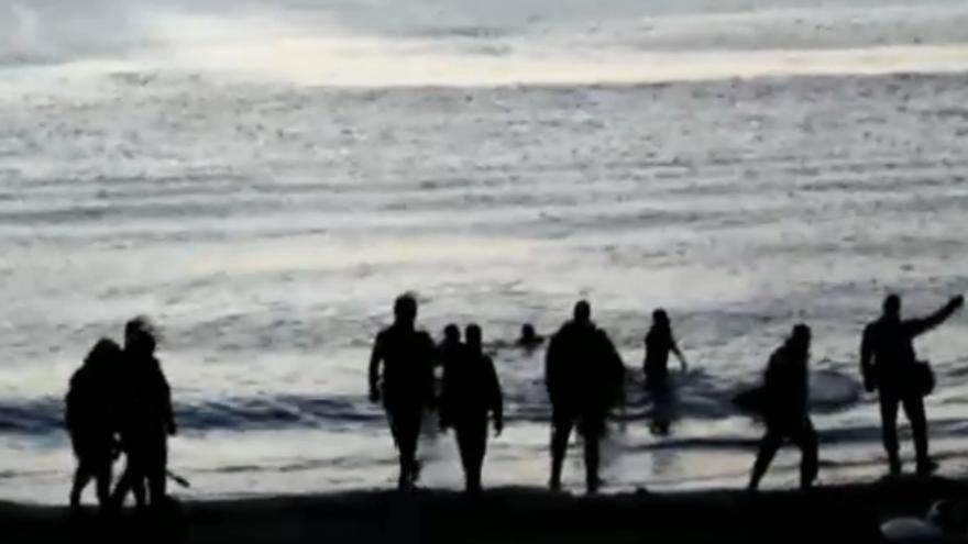 Imagen de la Guardia Civil con equipamiento antidisturbios recibiendo a los inmigrantes en la playa de Ceuta.