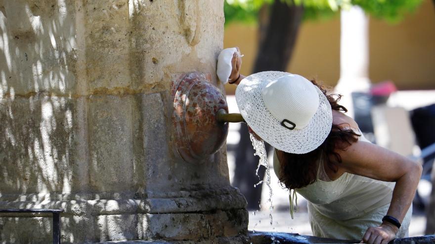 Una mujer se refresca en una de las fuentes de Córdoba.