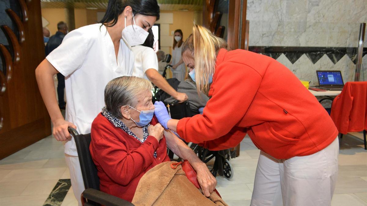 Una residente del centro Santa Eugenia de Palencia recibe la tercera dosis de la vacuna contra la COVUD-19