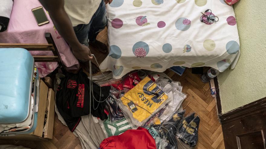 Serigne muestra en su habitación las camisetas de fútbol que no ha podido vender ante la imposibilidad de salir a la calle a vender por el coronavirus.