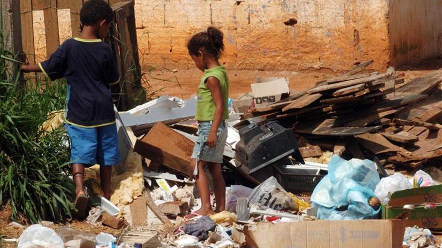 Imagen de archivo: Dos niños buscan entre la basura en Brasilia, Brasil.