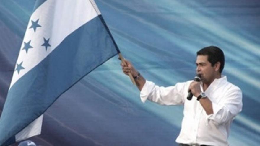 Juan Orlando Hernández, presidente de Honduras, hace flamear la bandera nacional con cinco estrellas, basada sobre la antigua bandera de las Provincias Unidas del Centro de América (Guatemala, El Salvador, Nicaragua, Honduras y Costa Rica),  basada a su vez sobre la de las Provincias Unidas del Río de la Plata.