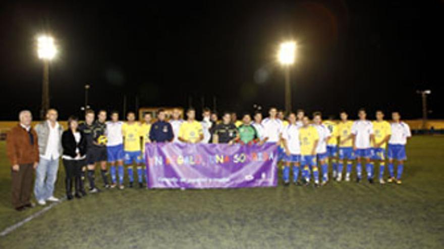 Jugadores de la U.D. Las Palmas, selección de Telde y autoridades sostienen la pancarta emblemática de la iniciativa solidaria. (ACFI PRESS)