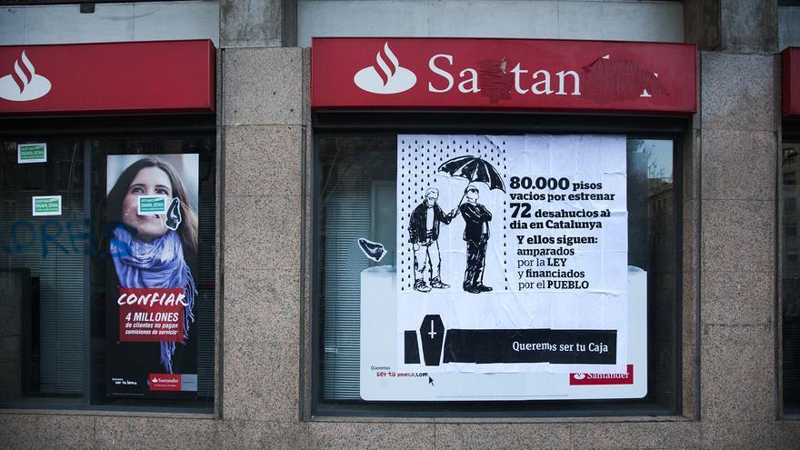 Cartel de protesta por los desahucios en una sucursal del Banco Santander en Barcelona. / ANDREA BOSCH.