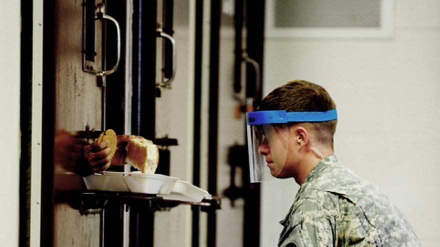 Un soldado de Guantánamo se asegura que un detenido del Campo 5 acepta la comida. 19 de octubre de 2011. © US DoD