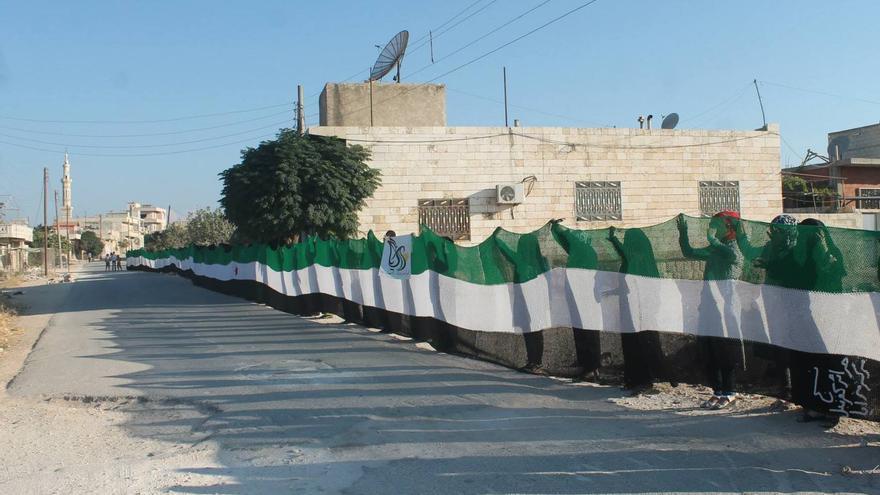 Mujeres del Centro Mazaya en Idlib sostienen la bandera revolucionaria más grande tejida en Siria. Fuente: página de la Revolución Siria en Facebook.