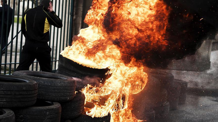 Un trabajador de SNIACE pasa por delante de unos neumáticos ardiendo en frente de las puertas de la factoría de Torrelavega, en uno de los cortes que han realizado a las entradas de la fábrica, durante las protestas por su situación laboral. | PEDRO PUENTE HOYOS (24/01/2014)
