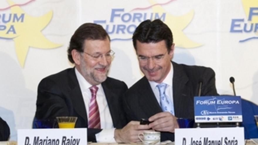 Entre Rajoy y Soria leen un mensaje de móvil. (ACFI PRESS)