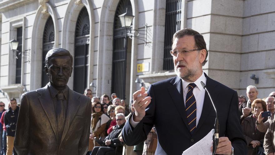 El candidato del PP a la Presidencia del Gobierno, Mariano Rajoy (i), durante su intervención ante el monumento en memoria del ex presidente del Gobierno Adolfo Suárez, el 4 de diciembre en Ávila.