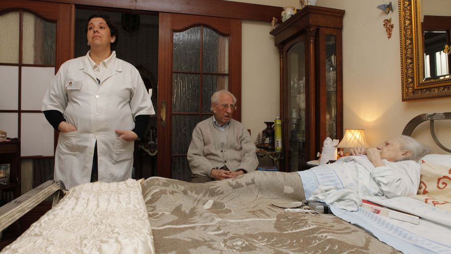 María, en la cama desde hace meses, junto a su marido y la auxiliar que los atiende a ambos.