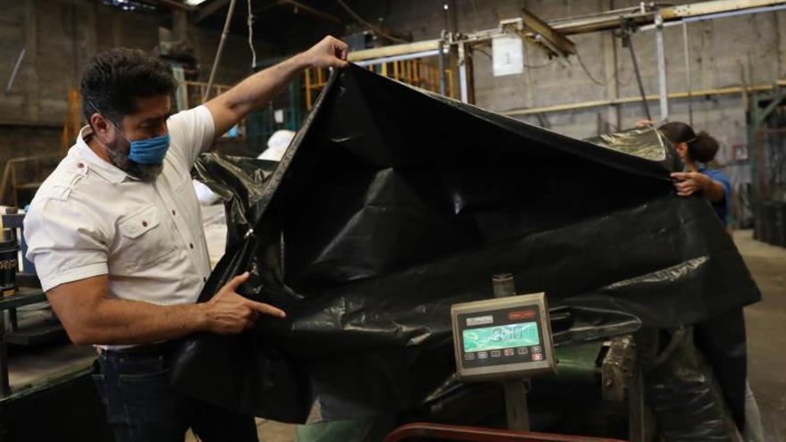 Empleados de la asociación de Recicladores Unidos de Bolsas Plásticas (Ruboplast), fabrican bolsas de plástico reciclado este jueves, en el municipio de Ecatepec en el Estado de México (México).