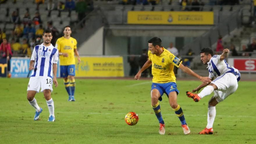 Vicente Gómez esconde el balón ante la presión de un jugador de la Real Sociedad.
