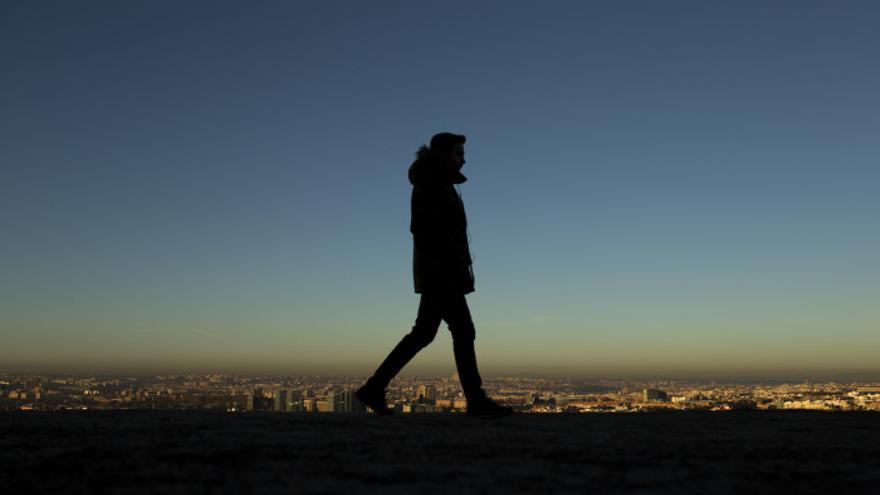 Una persona camina en Madrid, con la 'boina' de contaminación al fondo.