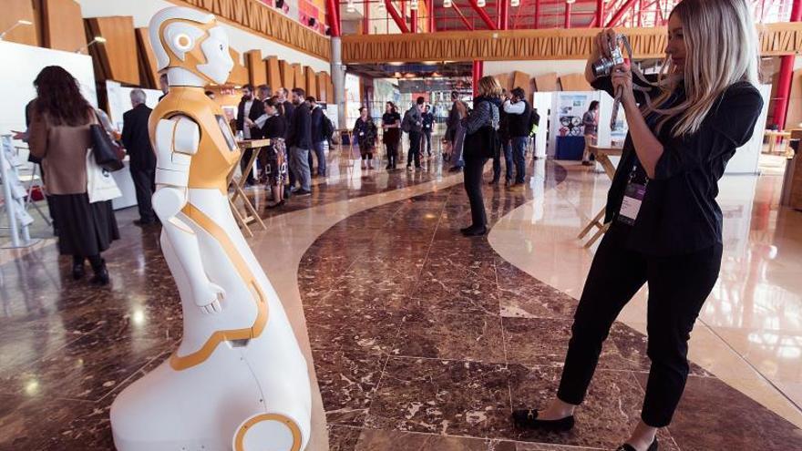 """Una asistente toma una fotografía a un robot, durante la celebración del """"European Robotics Forum"""", en el Palacio de Ferias y de Congreso de Málaga."""