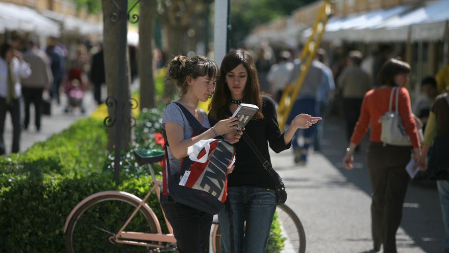 Dos jóvenes repasan un volumen en la Fira del Llibre de València.