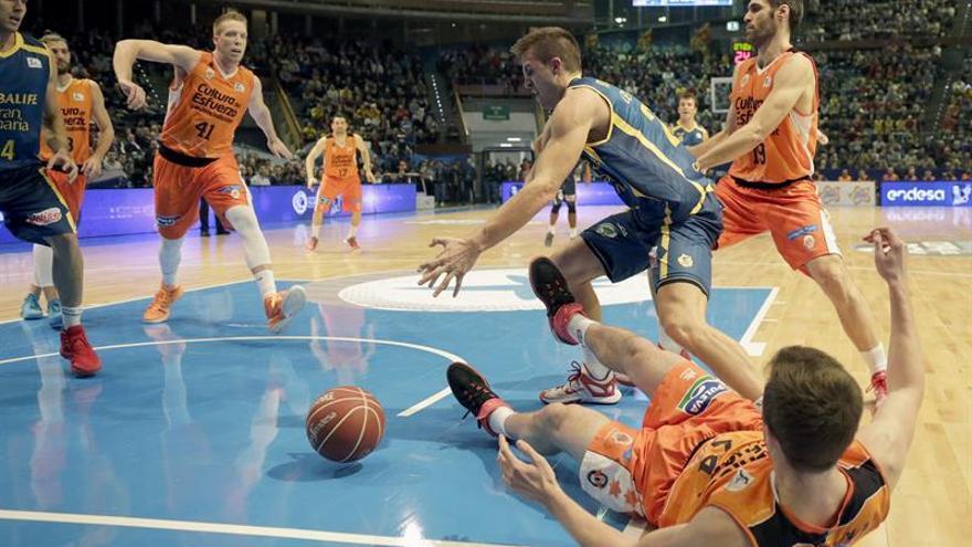 El alero del Herbalife Gran Canaria, Xavi Rabaseda (c), pelea un balón ante los jugadores del Valencia Basket, durante el partido de la segundo eliminatoria de los cuartos de final de la Copa del Rey de baloncesto, que se ha disputado en el Coliseum de A Coruña. EFE/Lavandeira jr.