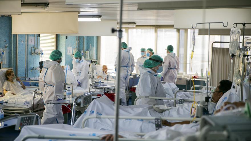 Trabajadores sanitarios atienden a numerosos pacientes en una de las UCI del Hospital Ramón y Cajal de Madrid