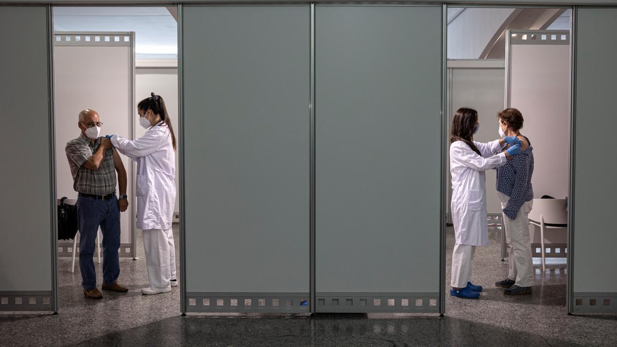 Dos personas reciben la segunda dosis de la vacuna contra la covid-19 de Pfizer en el centro de vacunación masiva instalado en la Ciudad de las Artes y las Ciencias de Valencia. EFE/Biel Aliño