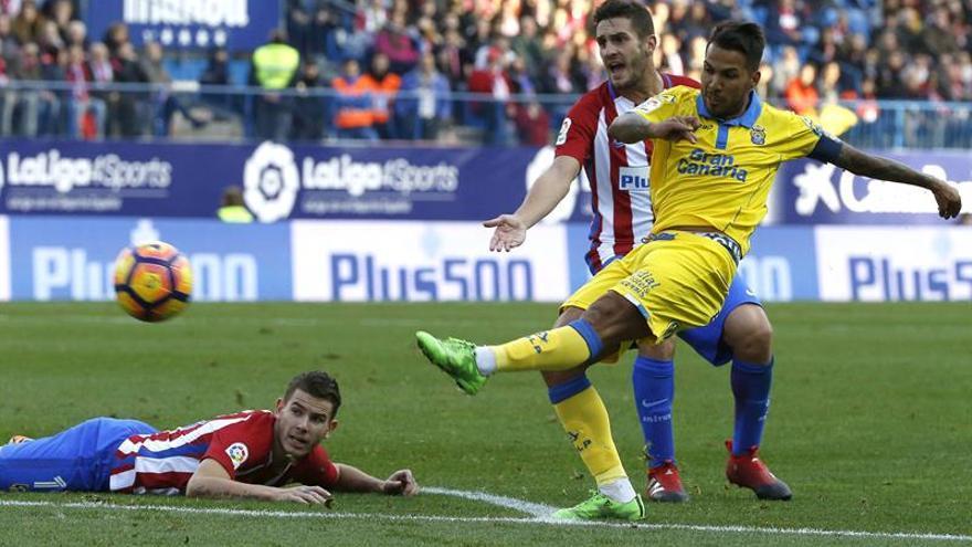 El centrocampista de Las Palmas Jonathan Viera (d) remata ante el centrocampista Koke Resurección (2d) y el defensa francés Lucas Hernández (i), del Atlético de Madrid, durante el partido de la decimosexta jornada de la Liga de Primera División en el Vicente Calderón, en Madrid. EFE/Kiko Huesca