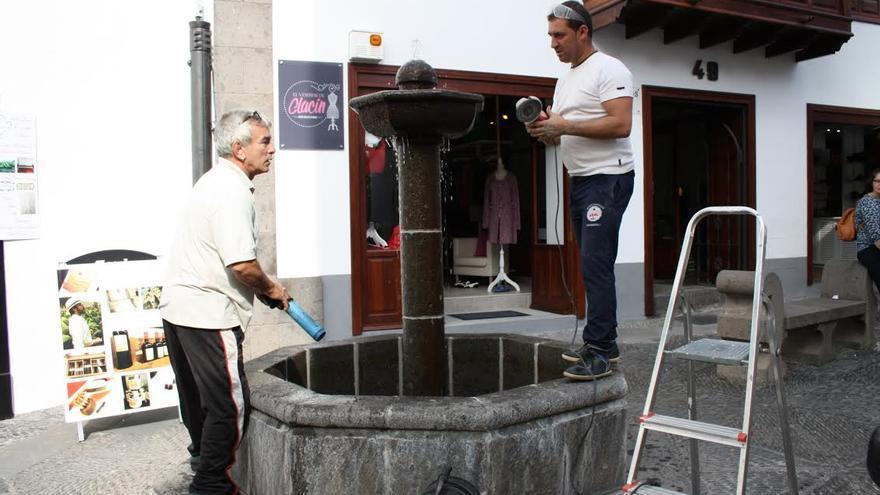 En la imagen, dos operarios del Ayuntamiento reparan la fuente de piedra.