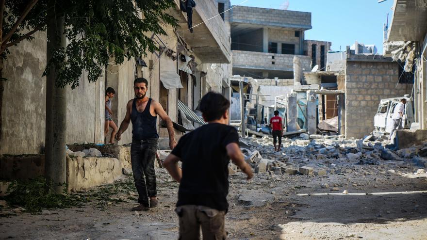 Un niño corre entre edificios destruidos en Idlib.