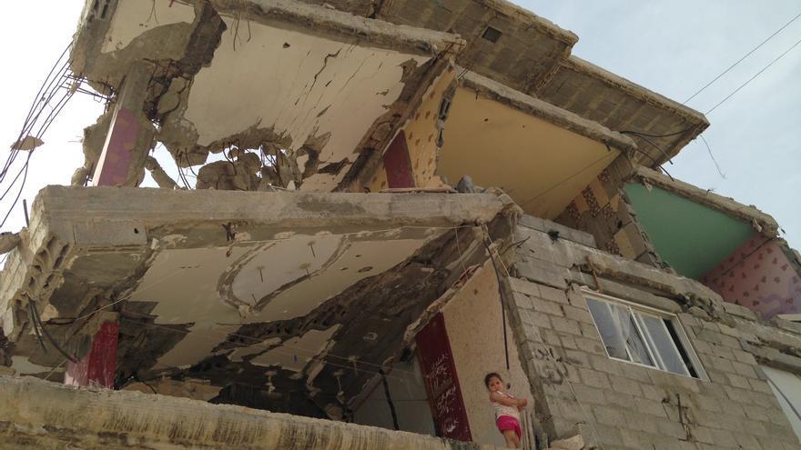 Una niña se asoma desde su casa destruida en Shejaya, Gaza