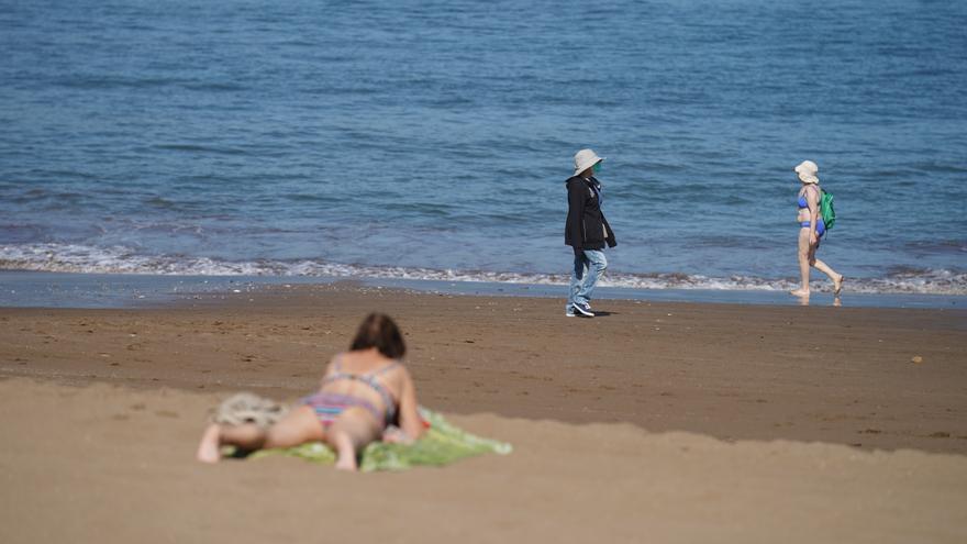 Archivo - Varias personas pasean y toman el sol en la Playa de Ereaga en Getxo