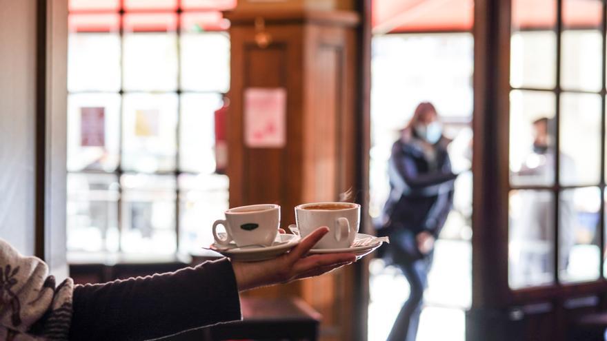 Archivo - Un camarero sirve varios cafés en una cafetería de Vitoria