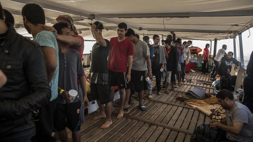 Los migrantes rescatados por el Open Arms hacen cola en el barco.