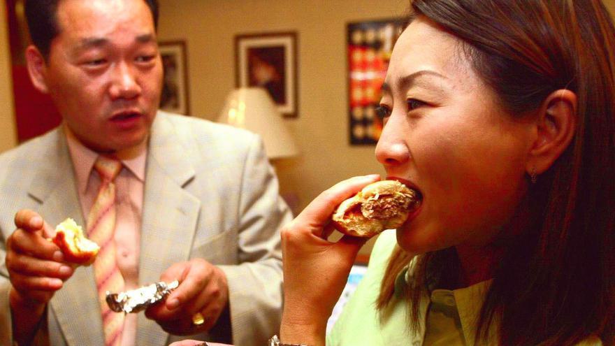 Dos personas coreanas comen una hamburguesa en un restaurante local.