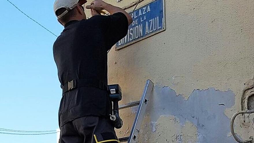 Un operario coloca de nuevo la placa de la 'Plaza División Azul' de Alicante